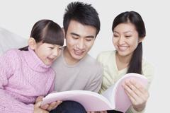 Family reading on the sofa, studio shot - stock photo