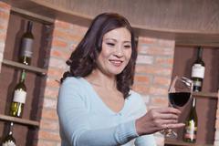 Mature Woman Looking at Wineglass, Winetasting - stock photo