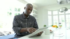 African American Man Using Digital Tablet At Home - stock footage