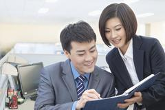 Two Business People Looking at Note Pad - stock photo