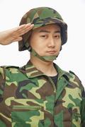 Portrait of man in military uniform saluting Stock Photos