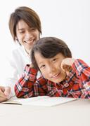 A boy studying with his father Stock Photos