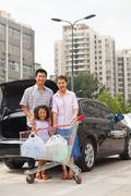 Family with shopping cart standing next to the car - stock photo