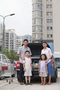 Family standing next to the car with shopping bags - stock photo