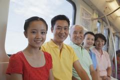 Family sitting in the subway, portrait - stock photo