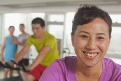 Woman smiling and exercising on the exercise bike Stock Photos