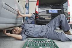 Mechanic Working on Underside of Car Stock Photos