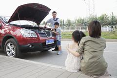 Mother and Daughter Watch as Father and Son Try to Fix the Car Stock Photos