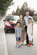 Family Portrait in Front of Car on Roadside - stock photo