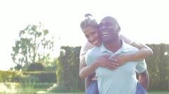 Mature Man Giving Woman Piggyback In Countryside - stock footage