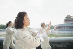 Three Chinese People Practicing Tai Ji Stock Photos
