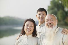 Three Chinese People With Tai Ji Clothes Smiling At Camera - stock photo