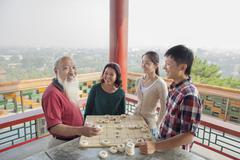 Chinese Family Playing Chinese Chess (Xiang Qi) - stock photo