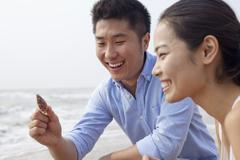 Young couple looking at seashell at the waters edge, China Stock Photos