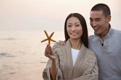 Young Couple Looking At a Seashell - stock photo