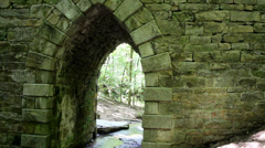 Looking through historic stone bridge arch Stock Footage