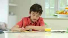 Hispanic Boy Doing Homework On Kitchen Counter Stock Footage