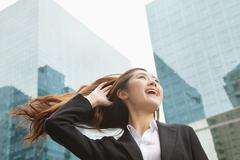Young Businesswoman with hair blowing in the wind, outdoors, Beijing Stock Photos
