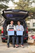 Father and son unpacking car for college - stock photo