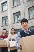 Family moving boxes into a dormitory at college - stock photo