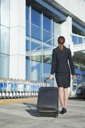 Traveler pulling suitcase into airport - stock photo