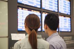 Two travelers looking at flight departure screens at airport - stock photo