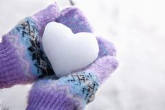 Snow Heart in Hands with Mittens Stock Photos