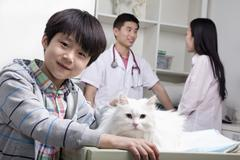 Boy with pet dog in veterinarian's office - stock photo