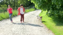 Children Running Along Country Path With Dog Stock Footage