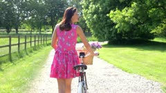 Attractive Woman Pushing Cycle Along Country Lane Stock Footage
