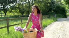 Attractive Woman Riding Bike Along Country Lane Stock Footage