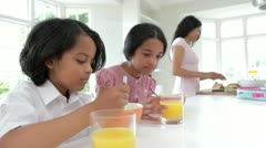 Stock Video Footage of Schoolchildren Having Breakfast Whilst Mother Makes Lunch