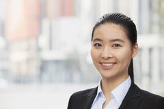 Portrait of smiling young businesswoman, head and shoulders - stock photo