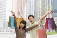 Portrait of young couple posing with shopping bags in hands, Beijing, China - stock photo