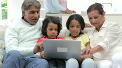 Multi-Generation Indian Family With Laptop Sitting On Sofa Stock Footage