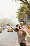Young couple with shopping bags hailing a taxicab in Beijing - stock photo
