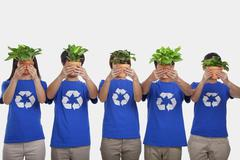 Group of people holding plants, obscuring faces, studio shot Stock Photos