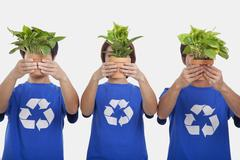 Three people holding plants, obscuring faces, studio shot - stock photo