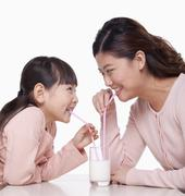 Mother and daughter sharing a glass of milk, studio shot - stock photo
