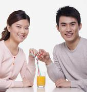 Young couple sharing a glass of orange juice, studio shot - stock photo