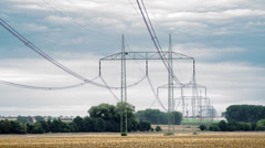 4K electrical pylons with time-lapsed cloudy sky Stock Footage