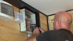 Worker Installing, Repairing a Security System, Man Setting a Secure Alarm - stock footage