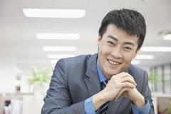 Portrait of Smiling Mid Adult Businessman Hands Clasped - stock photo