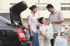 Family talking next to the car with shopping bags - stock photo