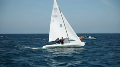 Two man sailing on sea with assistance boat in background - stock footage