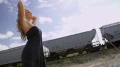 Redhead woman posing with train in bg Stock Footage