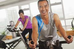 Man smiling and exercising on the exercise bike - stock photo