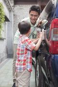 Father and Son Clean their Minivan Together Stock Photos
