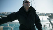 Stock Video Footage of Man on sailboat steering the boat
