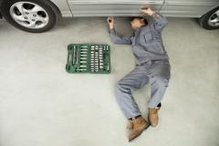 Mechanic Working on Underside of Car - stock photo